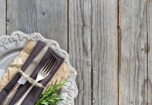 Vintage Table setting with napkin and plate on old wooden table
